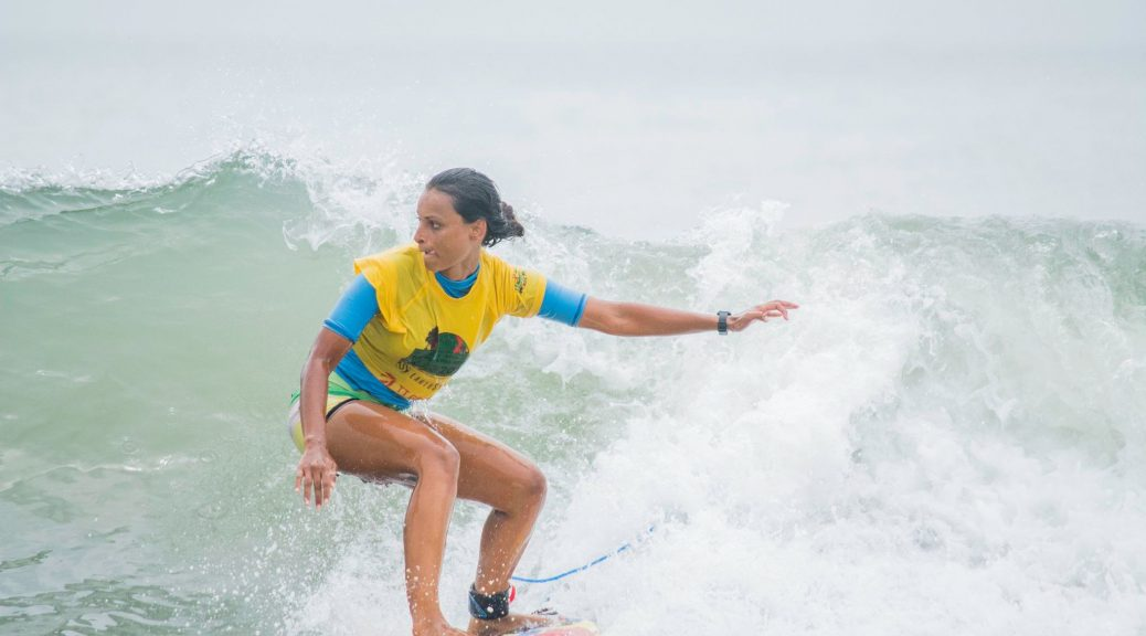 Surfer cuts through the waves at the Covelong Surf Festival 2016