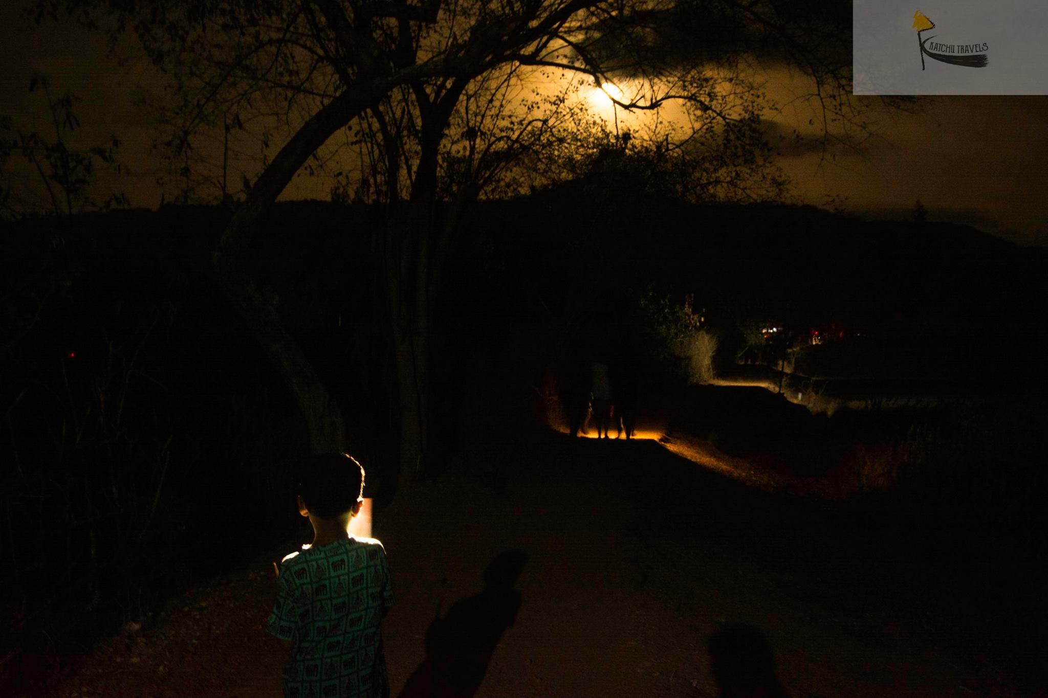 Nandu holding a mobile light against his face, as we walk back under the full moon light to our parking spot